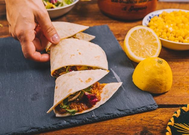 Primer plano de la mano de una persona que toma un trozo de tacos de carne mexicana