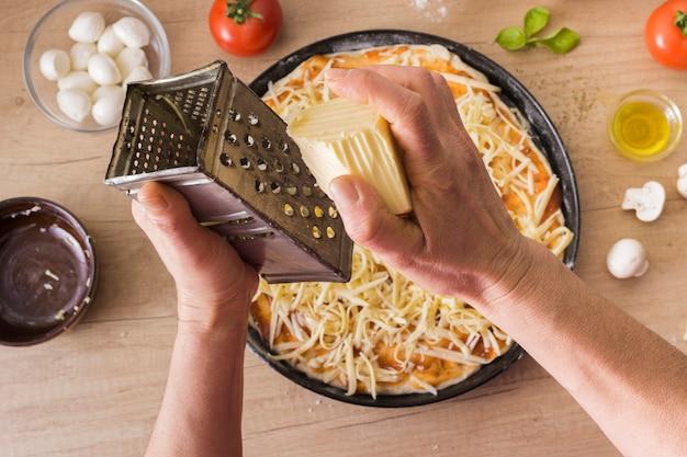 Primer plano de la mano de una persona rallando queso sobre la pizza cruda con ingredientes en el escritorio de madera