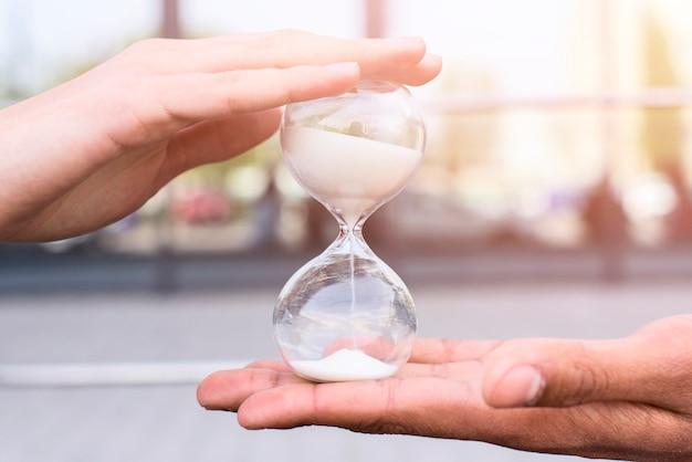 Primer plano de la mano de la persona con reloj de arena