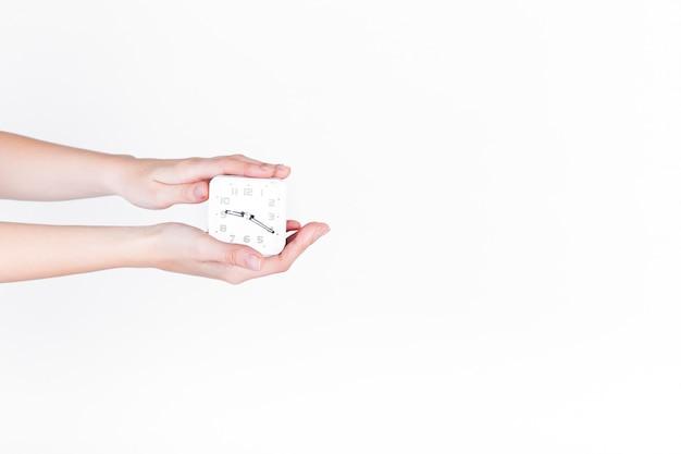 Primer plano de la mano de una persona con reloj despertador