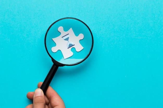 Primer plano de la mano de una persona sosteniendo una lupa sobre un ícono de reloj de arena en un rompecabezas blanco sobre un fondo azul
