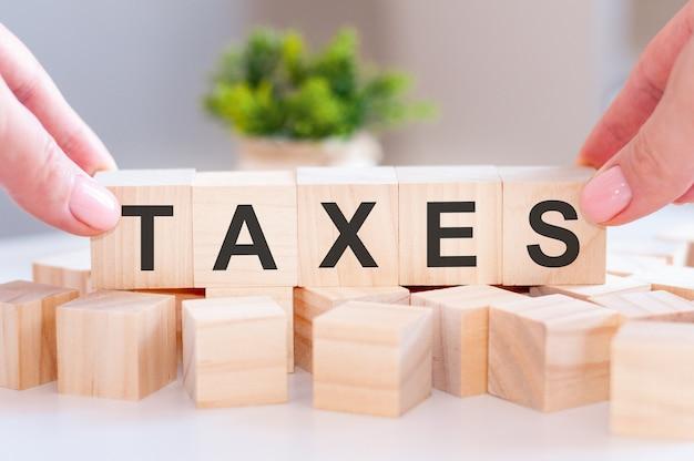 Primer plano de la mano de la persona sosteniendo la palabra impuestos sobre la mesa de madera. concepto de negocio. enfoque selectivo.