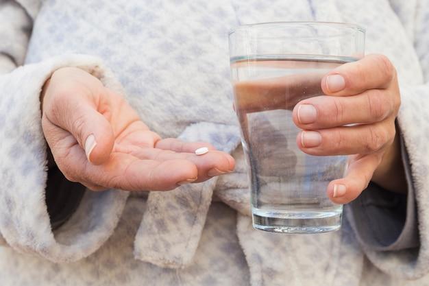 Primer plano de la mano de una persona sosteniendo una pastilla blanca y un vaso de agua