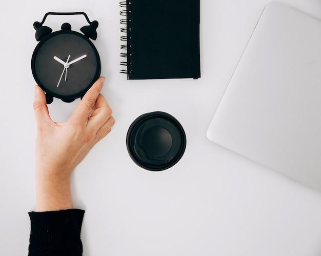 Primer plano de la mano de una persona sosteniendo un reloj despertador negro; bloc de notas espiral taza de café portátil y para llevar en el escritorio blanco