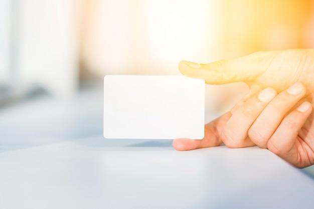 Primer plano de la mano de una persona sosteniendo la tarjeta blanca en blanco