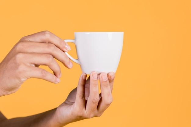 Primer plano de la mano de la persona sosteniendo la taza de té contra el telón de fondo amarillo