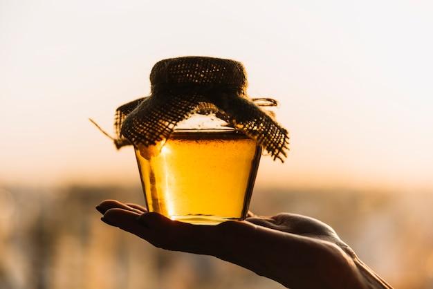 Primer plano de la mano de una persona con tarro de miel fresca