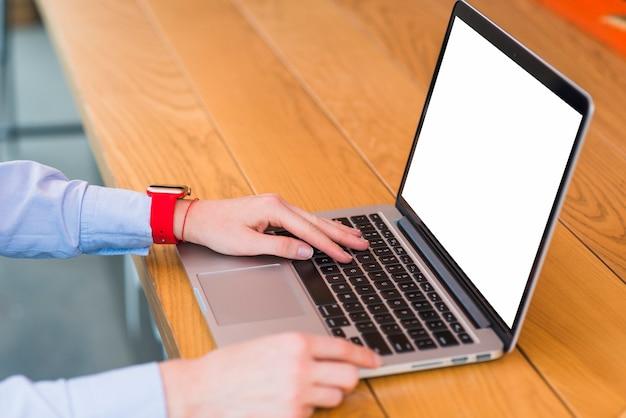 Primer plano de la mano de una persona usando una computadora portátil sobre un escritorio de madera