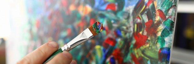 Primer plano de la mano de las personas creando pintura abstracta sobre lienzo. cuadro con colores mezclados. artista joven creativo y talentoso. obra maestra y concepto de arte moderno