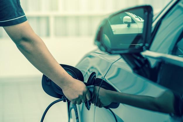 Primer plano de la mano que carga el auto eléctrico en el centro de servicio de mantenimiento que es parte de la sala de exposición, económico y tecnológico para la seguridad del mundo