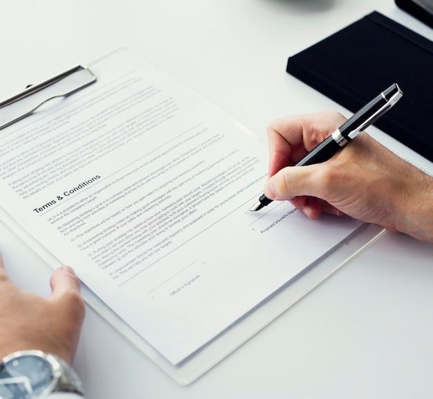 Primer plano de la mano que firma el espacio de trabajo de papel
