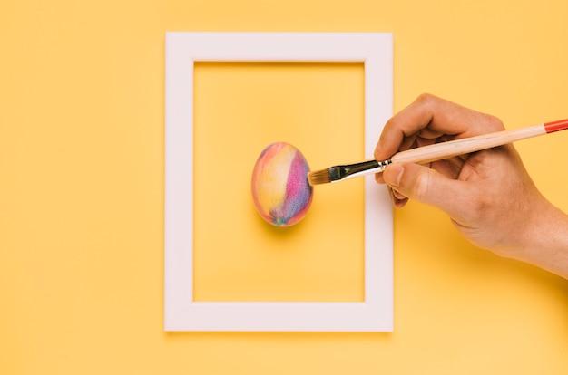 Primer plano de la mano que pinta el huevo de pascua con pincel dentro del marco sobre fondo amarillo