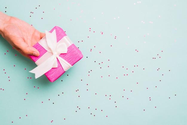 Primer plano de mano que sostiene una caja de regalo decorada con una cinta blanca sobre fondo azul