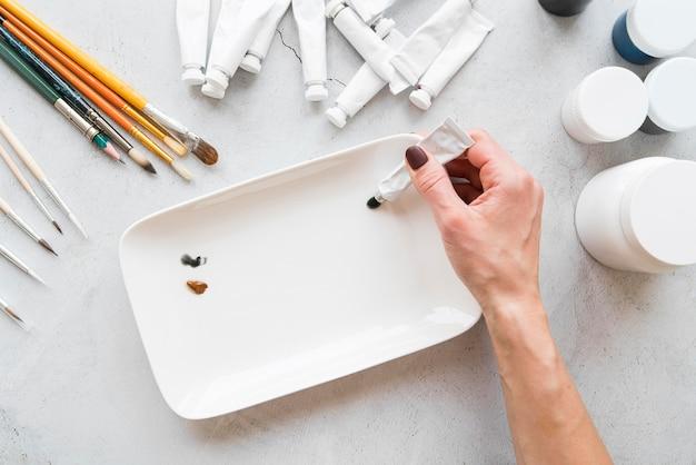 Primer plano mano que sostiene el contenedor de pintura