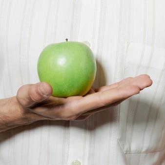 Primer plano de la mano que sostiene la manzana