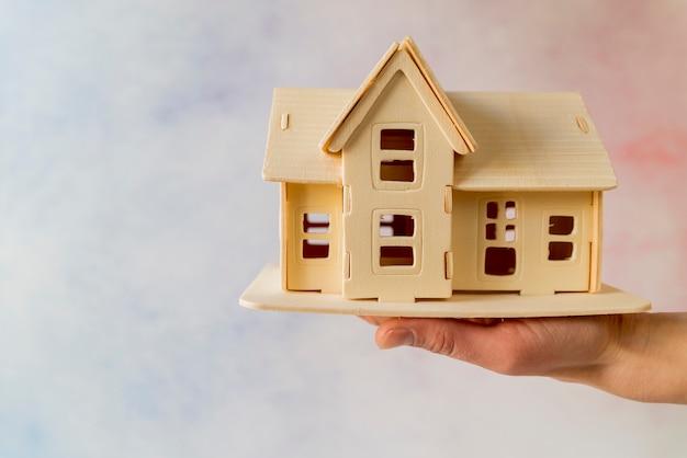 Primer plano de la mano que sostiene el modelo de casa contra el fondo con textura