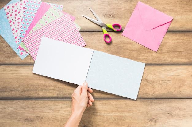 Primer plano de la mano que sostiene el papel de la tarjeta en blanco contra el telón de fondo de madera