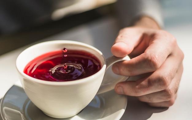 Primer plano de la mano que sostiene una taza de taza de té rojo recién hecho