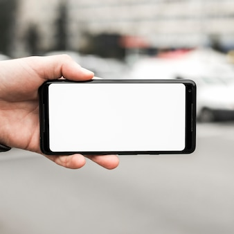 Primer plano de la mano que sostiene el teléfono móvil que muestra la pantalla en blanco en blanco