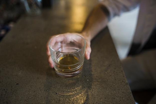 Primer plano de la mano que sostiene el vaso de whisky en el mostrador de la barra