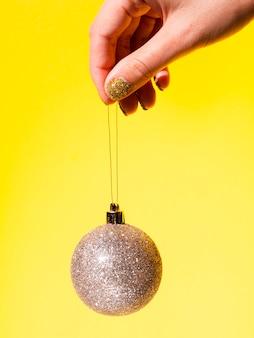 Primer plano mano sosteniendo bola de decoración