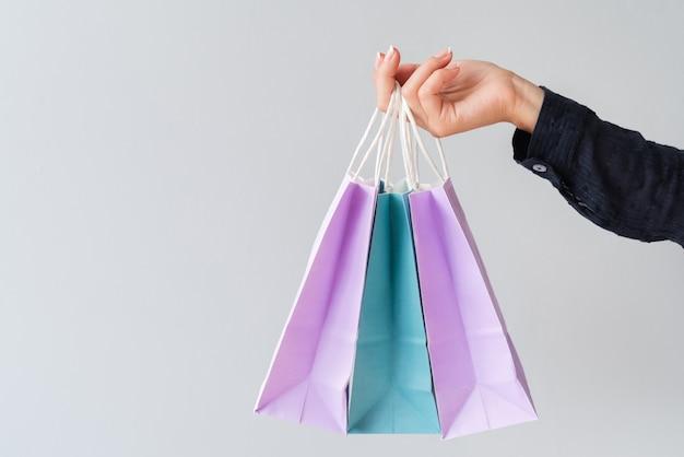 Primer plano de mano sosteniendo bolsas de regalo