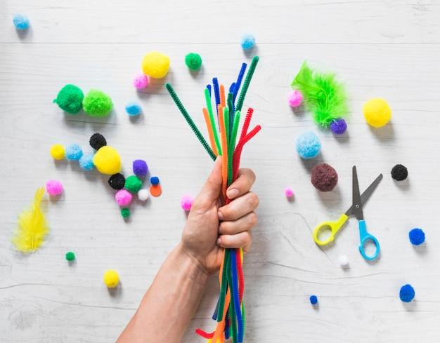 Primer plano de mano sosteniendo coloridos tallos de chenilla con elementos decorativos