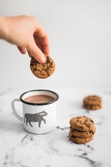 Primer plano de mano sosteniendo la cookie sobre la taza de té en el fondo de mármol