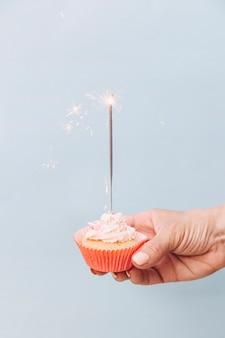 Primer plano de mano sosteniendo cupcake de cumpleaños con bengala sobre fondo gris