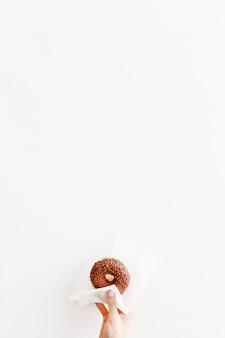 Primer plano de mano sosteniendo donut con papel de seda