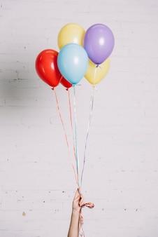 Primer plano de mano sosteniendo globos de colores en la mano contra la pared blanca