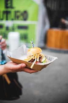 Primer plano mano sosteniendo una hamburguesa