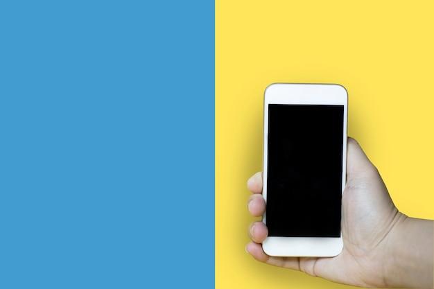Primer plano de una mano sosteniendo un teléfono móvil con un fondo azul-amarillo, utilizado para fotos publicitarias, trazado de recorte.