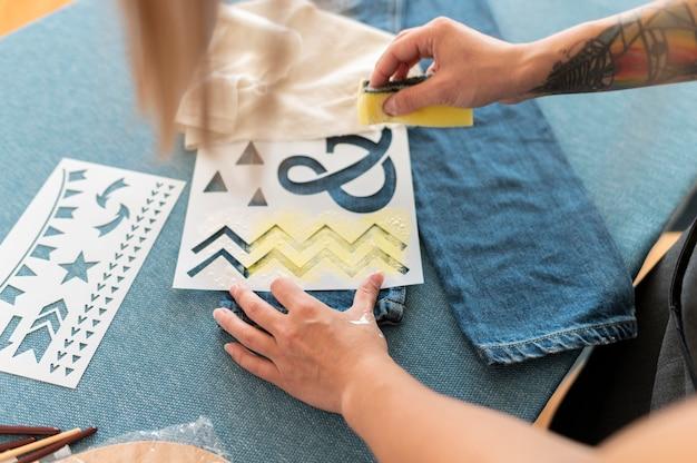 Primer plano mano sujetando una esponja con pintura