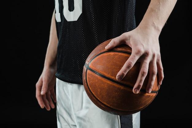 Primer plano de mano sujetando pelota de baloncesto