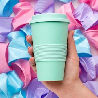 Primer plano mano sujetando una taza reutilizable