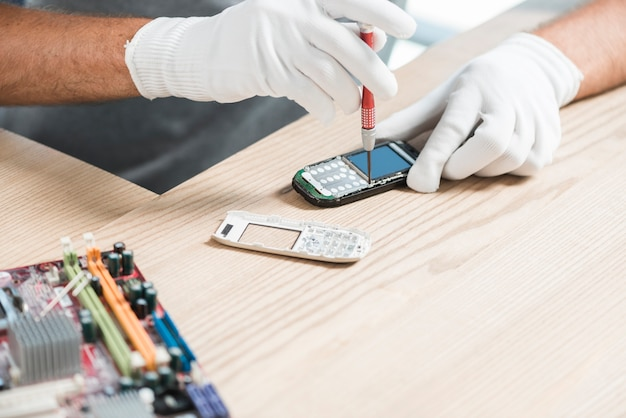 Primer plano de una mano técnico de reparación de teléfono móvil