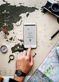 Primer plano de mano con teléfono móvil sobre fondo de mapa