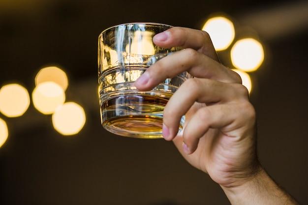 Primer plano, mano, tenencia, vaso de whisky