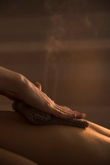 Primer plano de una mano de terapeuta masajeando la espalda de la mujer con una toalla caliente