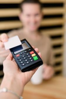 Primer plano de mano con terminal de pago