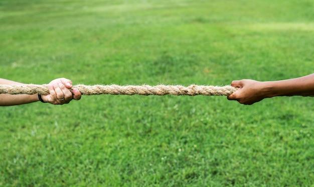 Primer plano de mano tirando de la cuerda en juego de tira y afloja Foto Premium