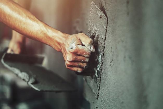 Primer plano de la mano del trabajador de enlucido de cemento en la pared para la construcción de la casa