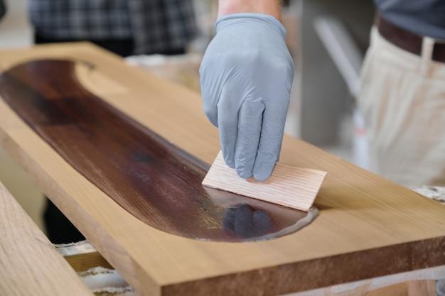 Primer plano de la mano del trabajador en guantes protectores con cubierta de acabado