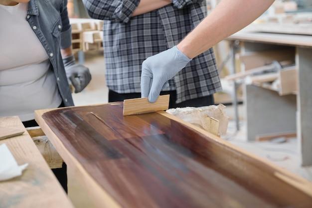 Primer plano de la mano de los trabajadores que cubre el tablón de madera con acabado de cubierta protectora para madera
