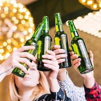 Primer plano de las manos de un amigo tintineando las botellas de cerveza
