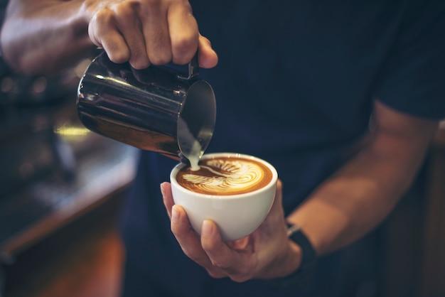 Primer plano de manos barista hacer café con leche arte pintura