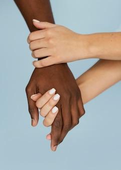Primer plano manos blancas sosteniendo la mano negra
