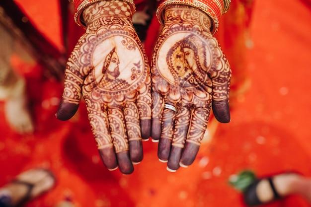 Primer plano de manos de una bonita novia hindú con tatuaje de henna