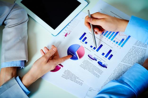 Primer plano de las manos con cartas financieras en la reunión de negocios